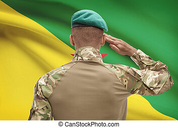 Dark-skinned soldier with flag on background - French Guiana...
