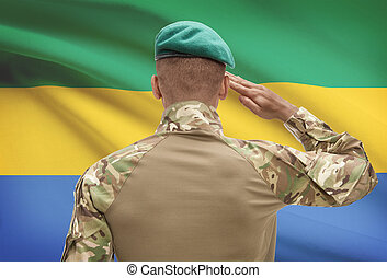 Dark-skinned soldier with flag on background - Gabon -...