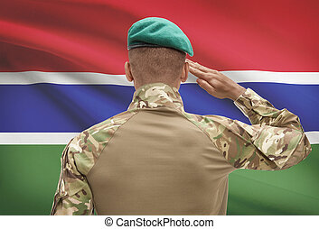 Dark-skinned soldier with flag on background - Gambia -...