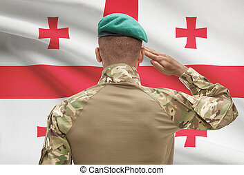Dark-skinned soldier with flag on background - Georgia -...
