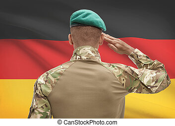 Dark-skinned soldier with flag on background - Germany -...