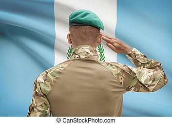 Dark-skinned soldier with flag on background - Guatemala -...
