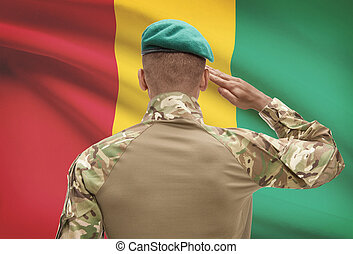 Dark-skinned soldier with flag on background - Guinea -...