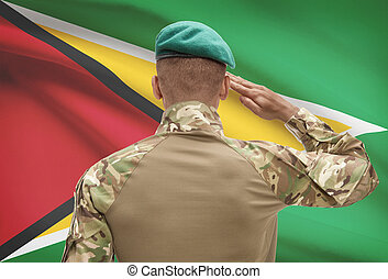 Dark-skinned soldier with flag on background - Guyana -...