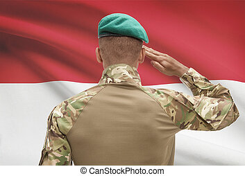 Dark-skinned soldier with flag on background - Indonesia -...