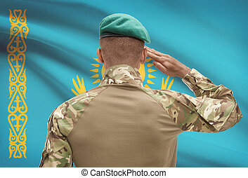 Dark-skinned soldier with flag on background - Kazakhstan -...