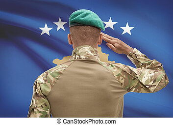 Dark-skinned soldier with flag on background - Kosovo -...