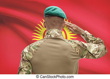 Dark-skinned soldier with flag on background - Kyrgyzstan -...