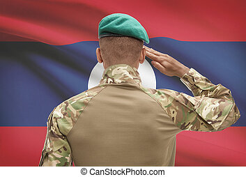 Dark-skinned soldier with flag on background - Laos -...
