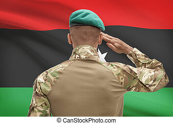 Dark-skinned soldier with flag on background - Libya -...