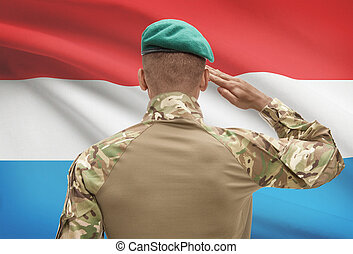 Dark-skinned soldier with flag on background - Luxembourg -...