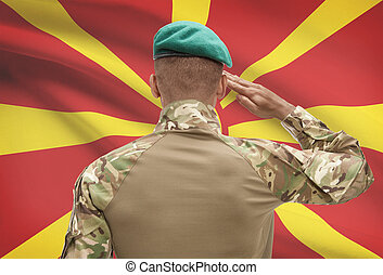 Dark-skinned soldier with flag on background - Macedonia -...