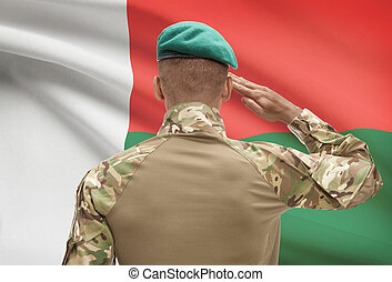 Dark-skinned soldier with flag on background - Madagascar -...