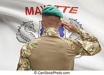Dark-skinned soldier with flag on background - Mayotte -...