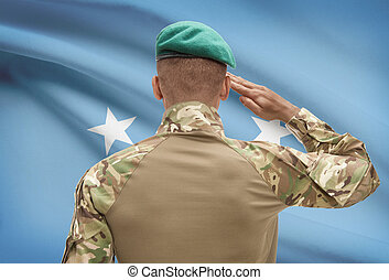 Dark-skinned soldier with flag on background - Micronesia -...