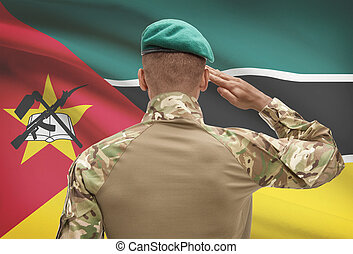 Dark-skinned soldier with flag on background - Mozambique -...