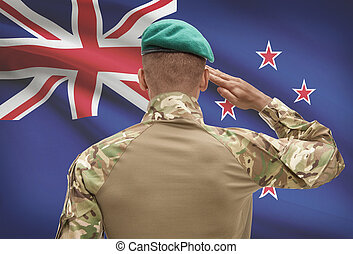 Dark-skinned soldier with flag on background - New Zealand -...