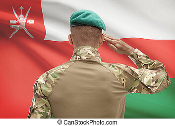 Dark-skinned soldier with flag on background - Oman -...