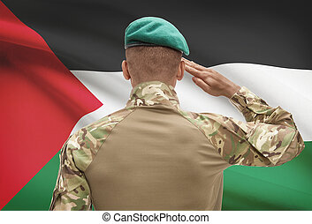 Dark-skinned soldier with flag on background - Palestine -...