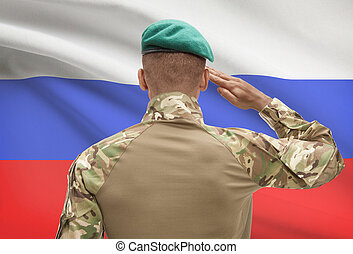 Dark-skinned soldier with flag on background - Russia -...