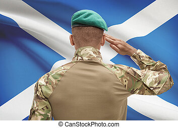Dark-skinned soldier with flag on background - Scotland -...