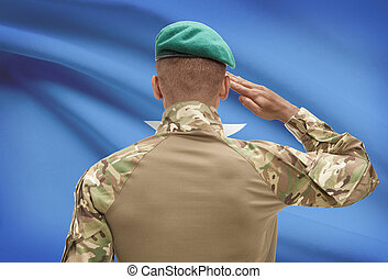 Dark-skinned soldier with flag on background - Somalia -...