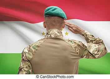 Dark-skinned soldier with flag on background - Tajikistan -...