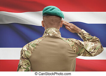 Dark-skinned soldier with flag on background - Thailand -...
