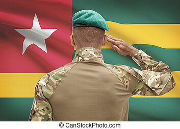 Dark-skinned soldier with flag on background - Togo -...