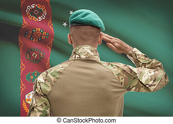 Dark-skinned soldier with flag on background - Turkmenistan...