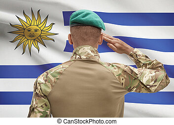 Dark-skinned soldier with flag on background - Uruguay -...