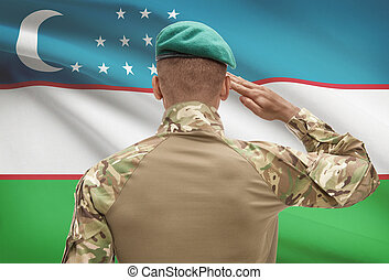 Dark-skinned soldier with flag on background - Uzbekistan -...