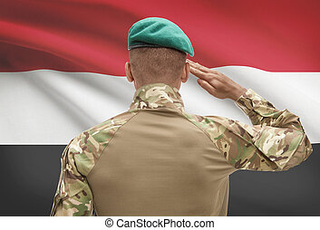 Dark-skinned soldier with flag on background - Yemen -...