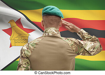 Dark-skinned soldier with flag on background - Zimbabwe -...
