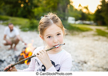 Little girl eating roasted marshmallow by a self-made...