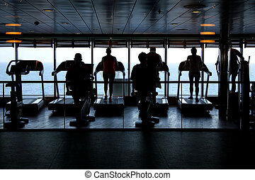 People exercising at the gym on a cruise ship in silhouette...