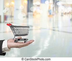 Hand holding small 3D empty shopping cart