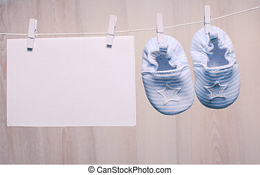 Baby boy booties attached to the rope and blank card for...
