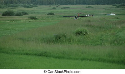 Small airplane landing on remote airstrip in field in the...