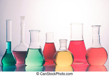 Laboratory glass with rainbow color liquids, chemistry still...
