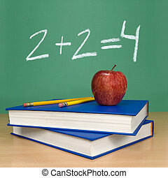 Basic sum - 2 + 2 = 4 written on a chalkboard. Books,...