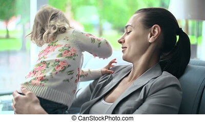 Busy Mother of a Carefree Child - Mother hugging her...