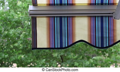 Detail of modern striped awnings in the rain