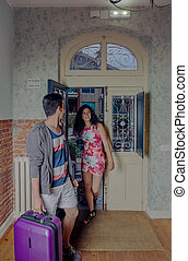 Young couple with suitcases arriving to a hostel - Happy...
