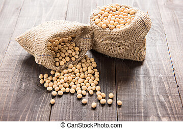 Soybean in a bag on wooden background. - Soybean in a bag on...