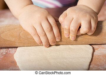 Children hands kneading dough