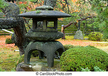 Granite lantern in the middle of wild garden
