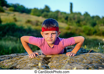 Sporty Young Boy Doing Push up on Top of Boulder