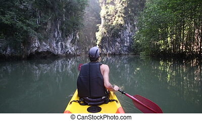 old man paddles on kayak down calm river to turn among...