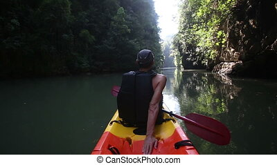old man drifts on kayak down calm river rests looks around -...